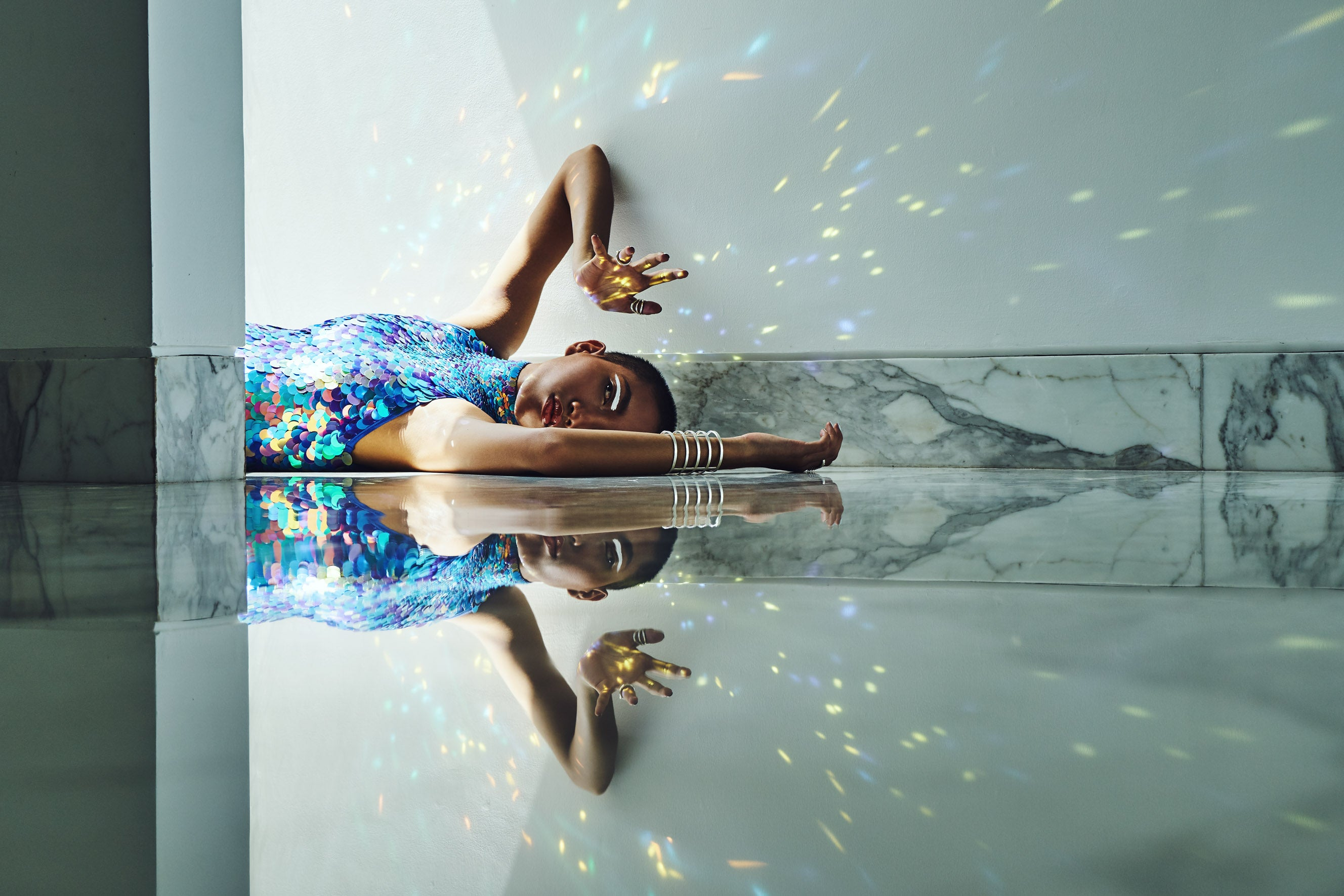 "woman wearing a high neck leotard covered with round iridescent blue sequins lays against a white marble wall"" /><img src="
