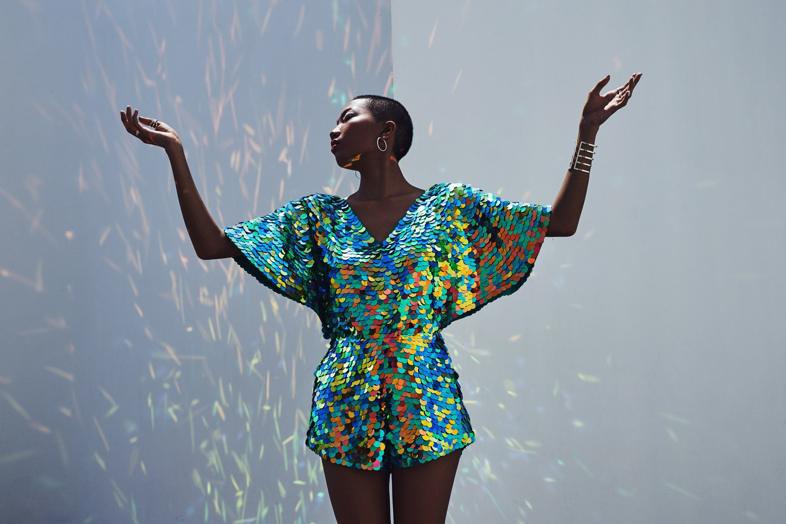 woman holds up her arms wearing a cape sleeved playsuit  wearing a v neck top covered with large round blue sequins