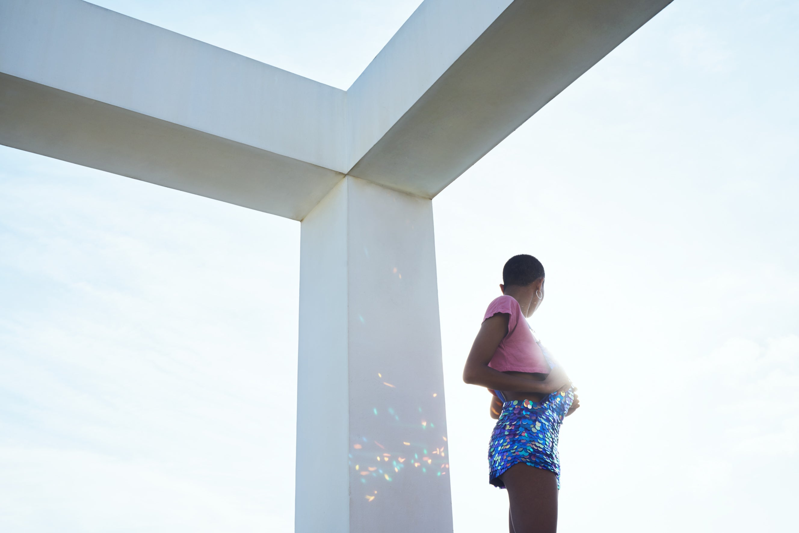 woman wearing a  pink crop top and dungaree shorts covered in large round iridescent blue sequins looks into the blue sky