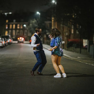 A newlywed couple dance in the street at night.