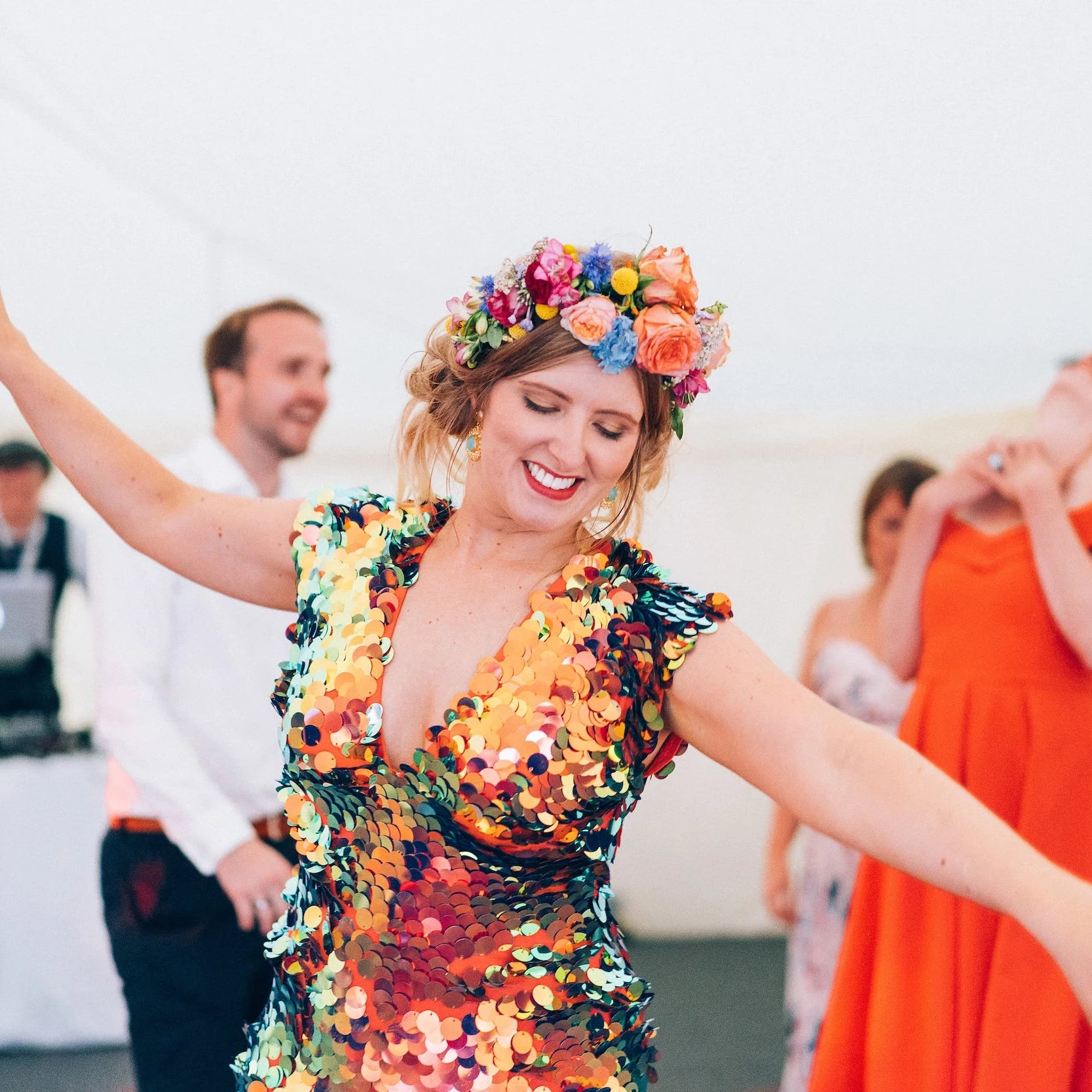 A bride wears a colourful headdress and full sequin jumpsuit
