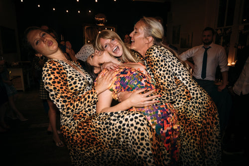 A bride wearing a festival style sequin jumpsuit is being embraced by several of her bridesmaids who are all wearing leopard print.