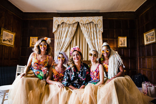 A bride wearing a festival style headdress sits with her bridesmaids on the morning of her wedding and they are all wearing sun glasses and pink sequin playsuits.