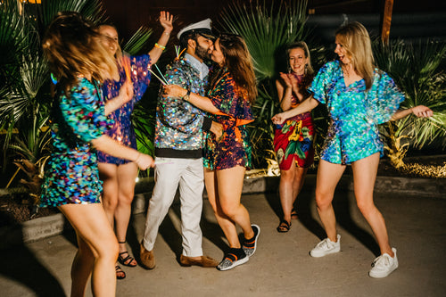 A bride and groom wearing bright sequin clothing are surrounded by friends all wearing bright sequin outfits.