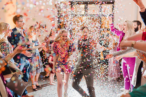 A festival style bride and groom walk into a could of confetti at ther wedding.