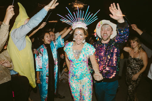 A festival style bride wearing an ornate headdress and white sequin jumpsuit holds hands with her partner who is also wearing a sequin bomber jacket with a cowboy hat.