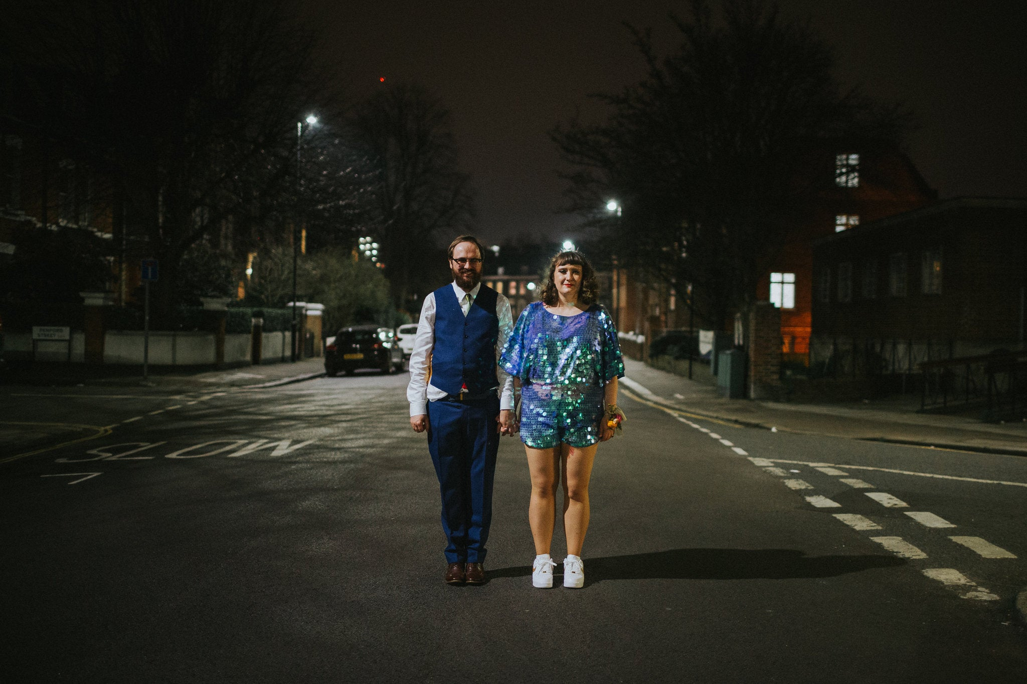 A bride wearing a blue sequin romper stands with her husband at night in a city street.
