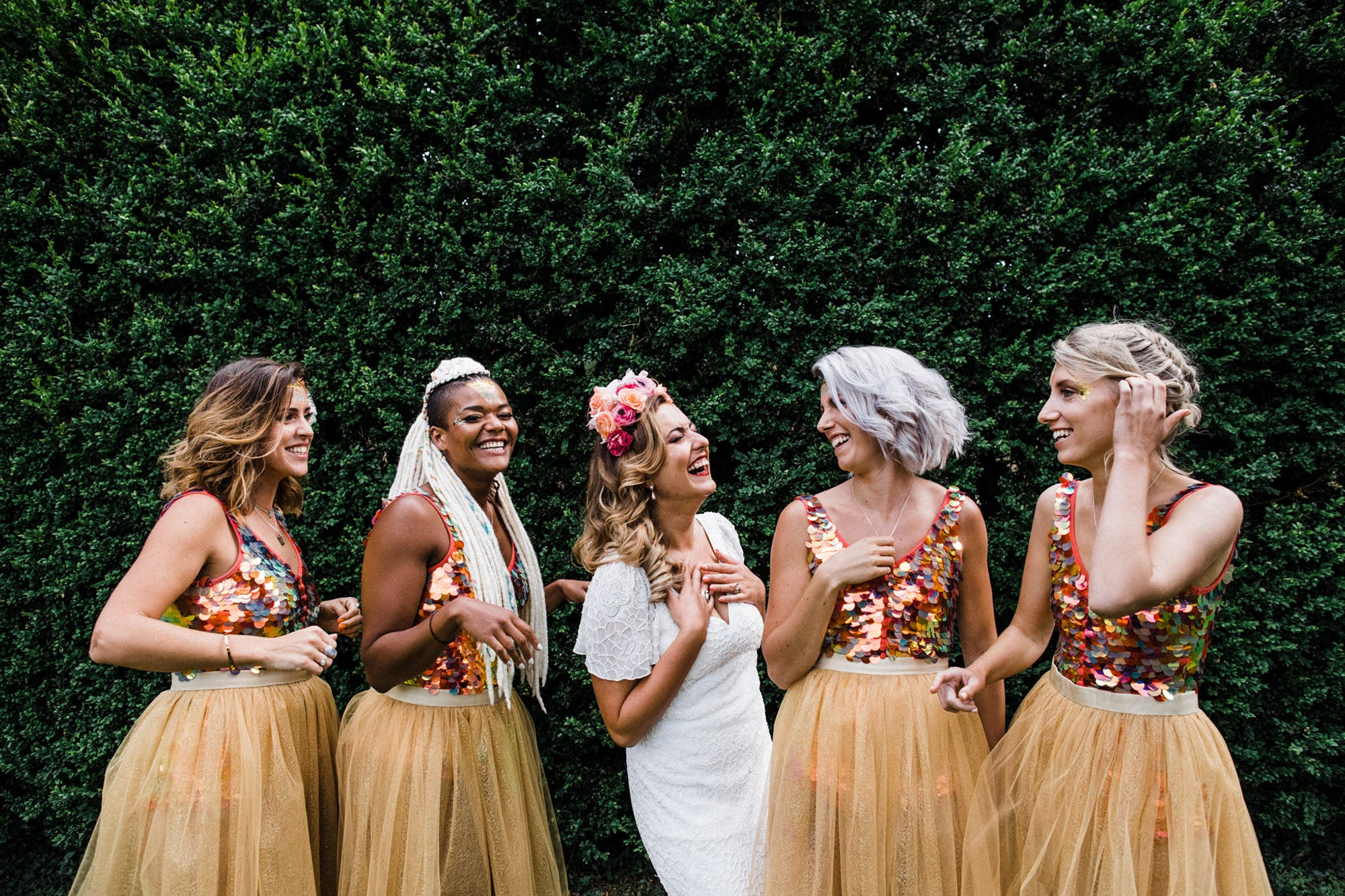 Bride stands with her bridesmaids who all wear sequin clothing