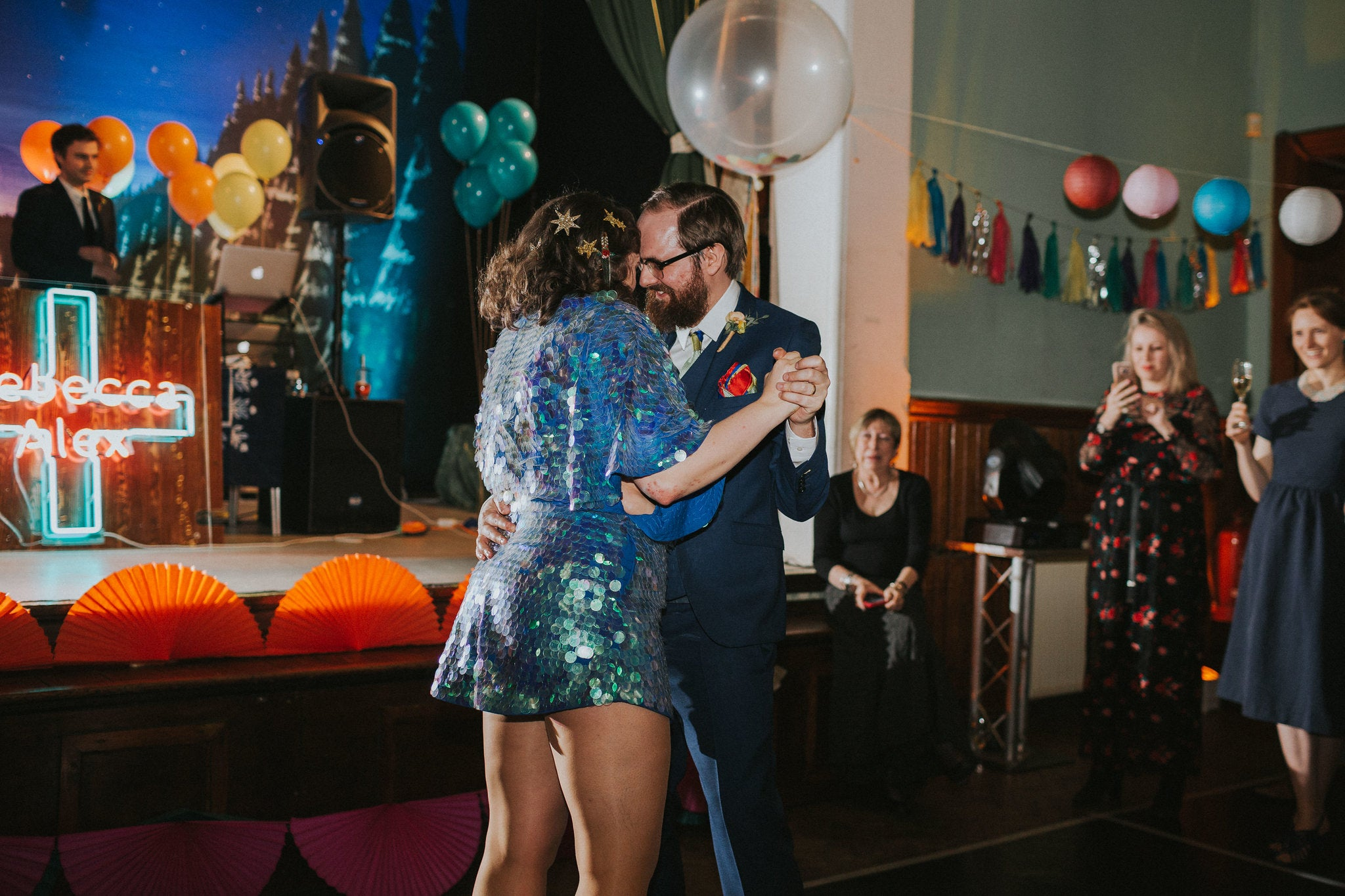 A bride wearing a blue sequin romper dances with her husband at the wedding.