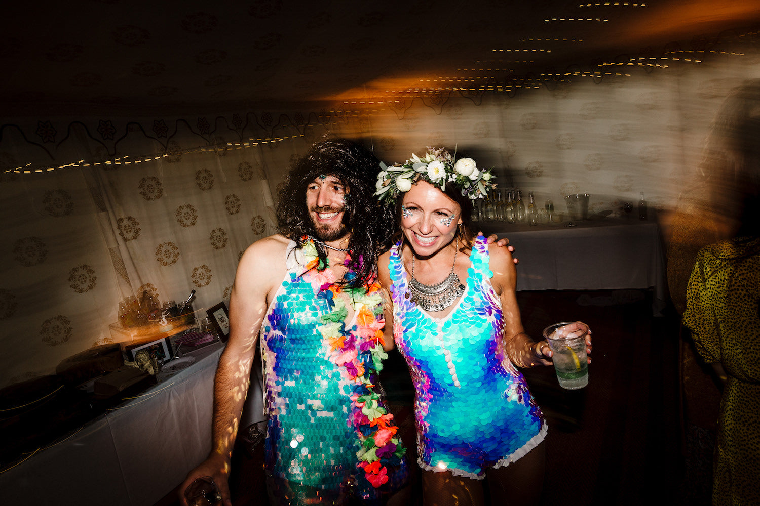 A bride wearing a white sequin playsuit poses with a male wedding guest wearing a sequin dress and a long black wig.