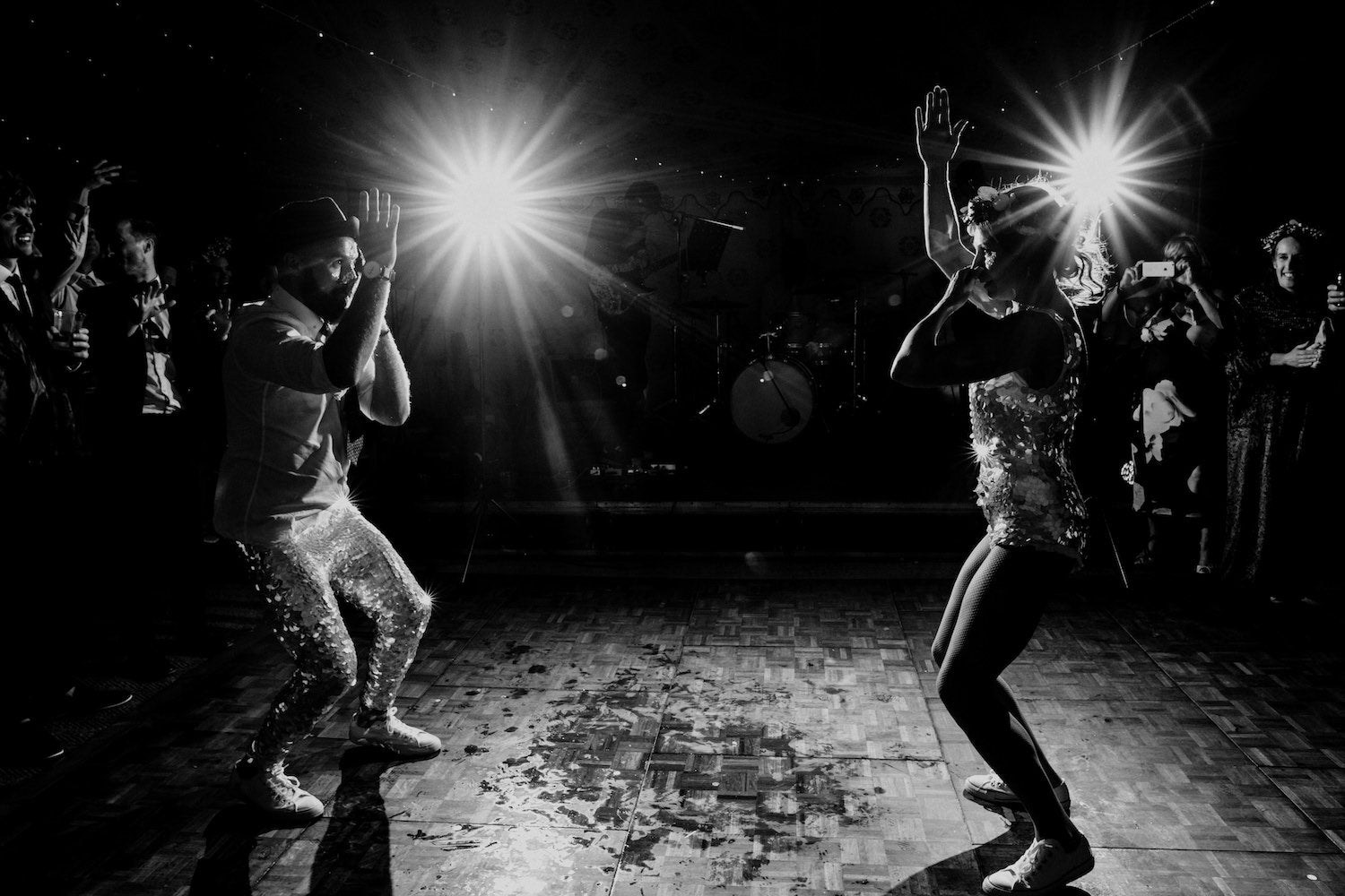 A black and white image of a bride a groom wearing matching sequin outfits poerforming their first dance at their wedding reception.