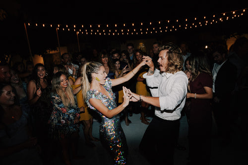 Festival style bride in a sequin jumpsuit dancing  with the groom.