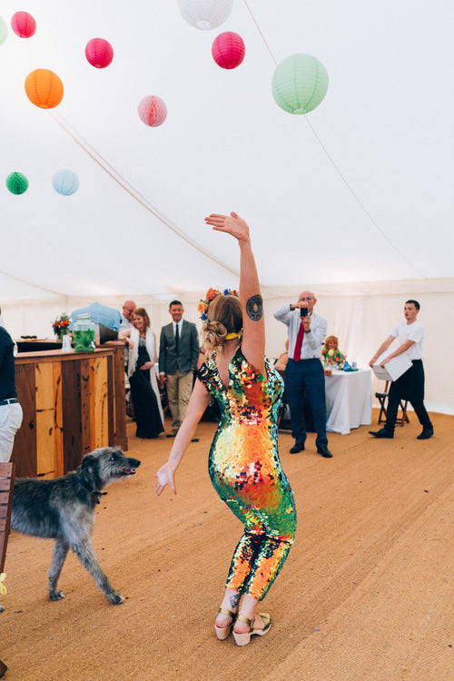 A bride wearing a festival style red sequin jumpsuit strikes a pose on the dancefloor at her wedding.