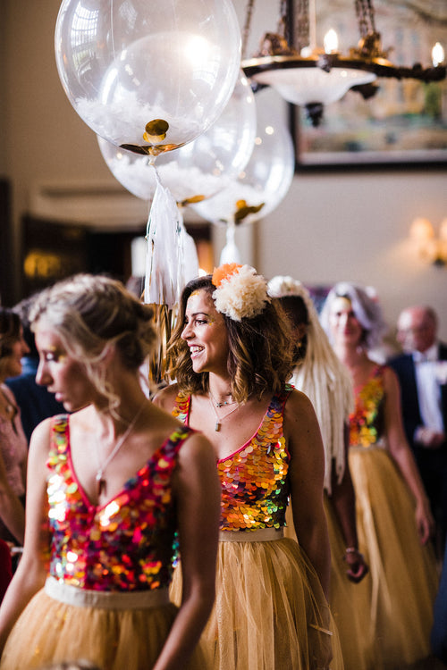 A row of bridesmaids all wearing festival style playsuits and pom-poms in their hair.