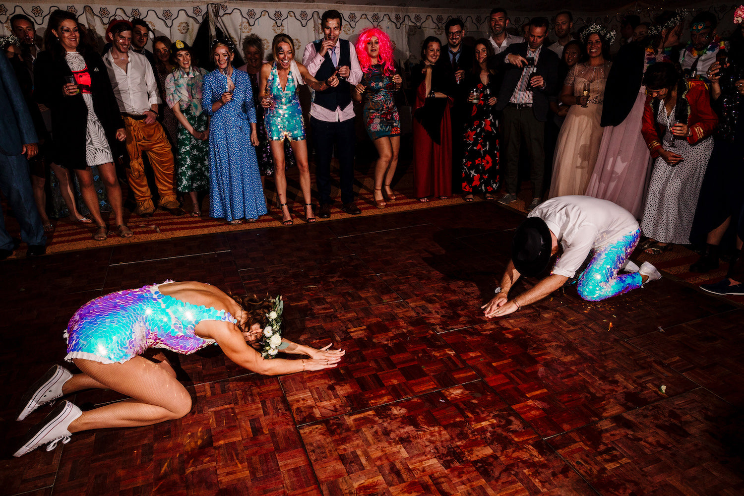 A bride and groom wearing matching white sequin outfits are picutred in the middle of performing a choreographed dance at their reception.