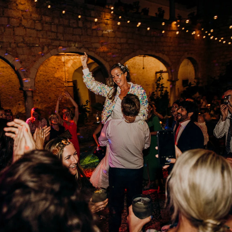 A bride wearing a festival style sequin bomber jacket is lifted up by her husband on the dancefloor.