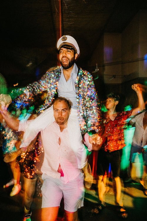 A groom wearing a festival style sequin bomber jacket  and sailor hat sits on the shoulders of his friend at his wedding.