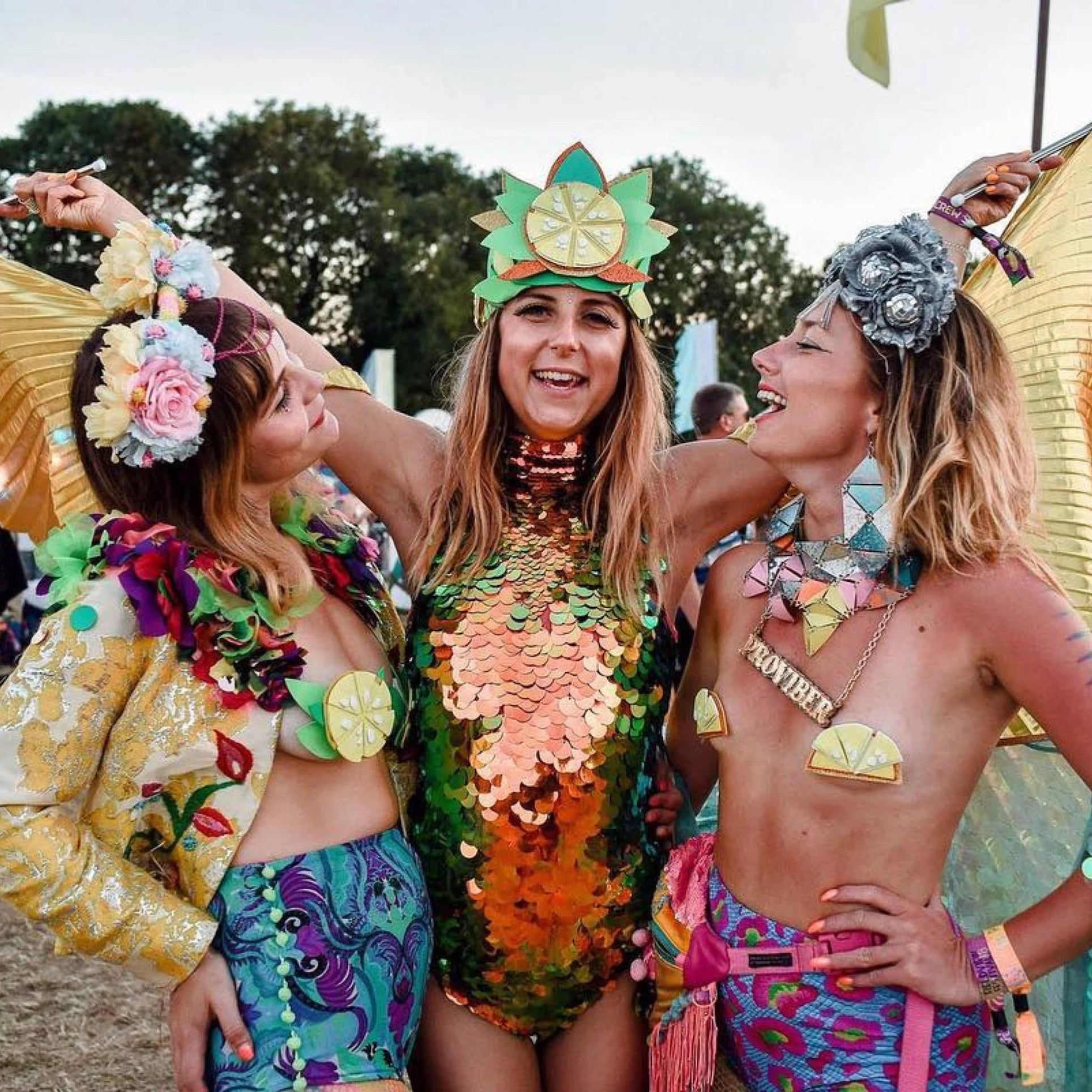 Three friends in sequin clothing at a festival
