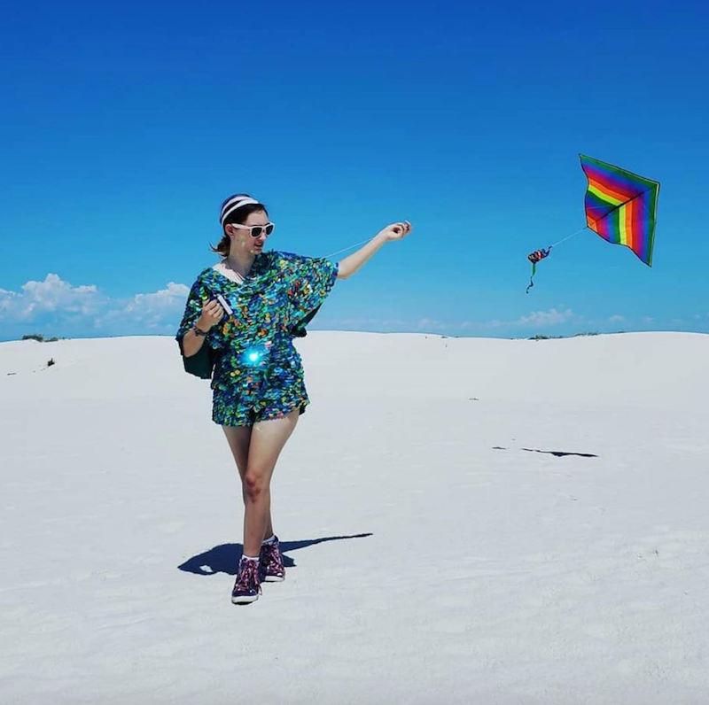 A woman in a sequin romper flying a rainbow kite at White Sands