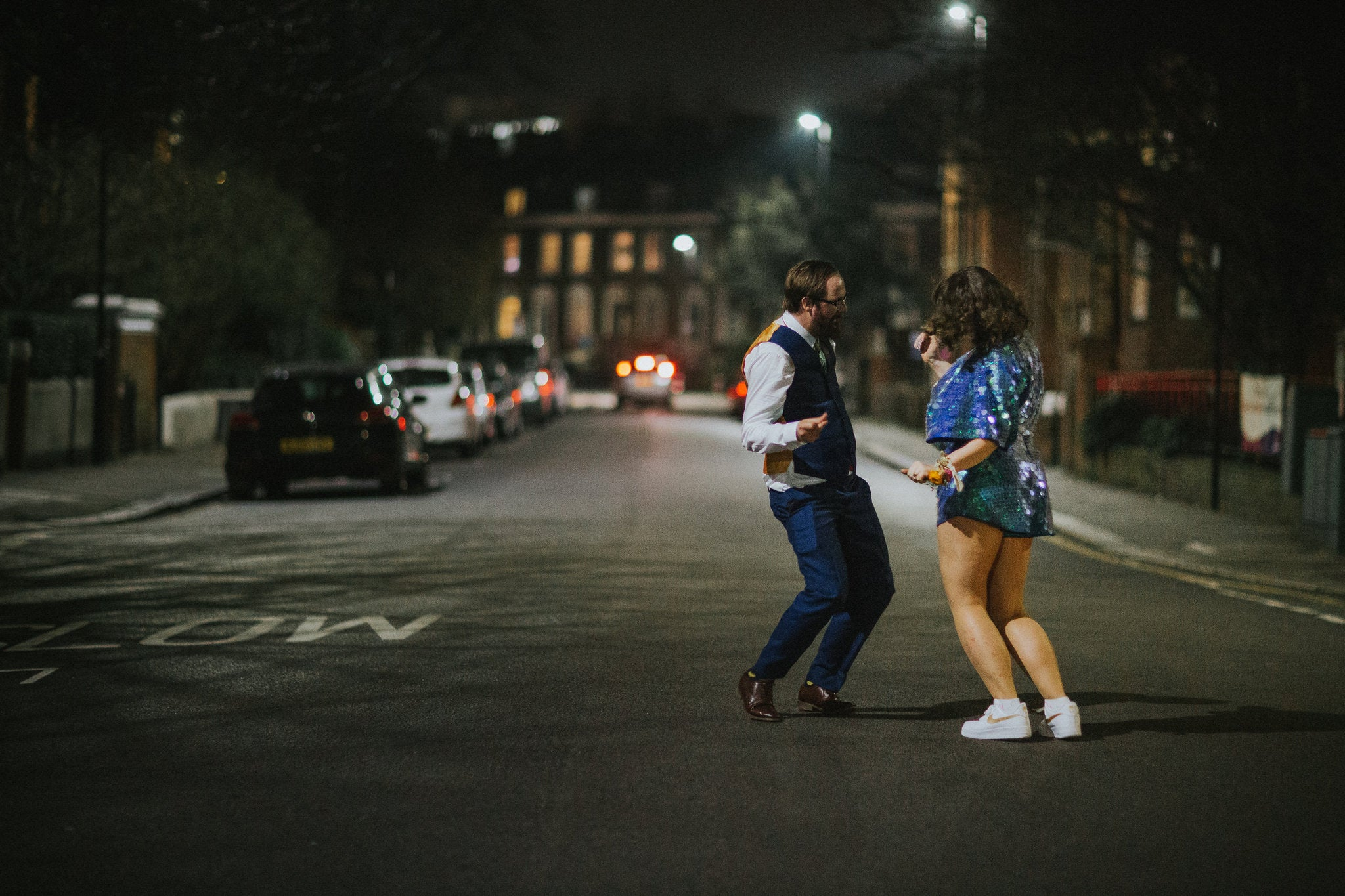 Woman wearing a blue sequin romper dances with a man in the street at night.