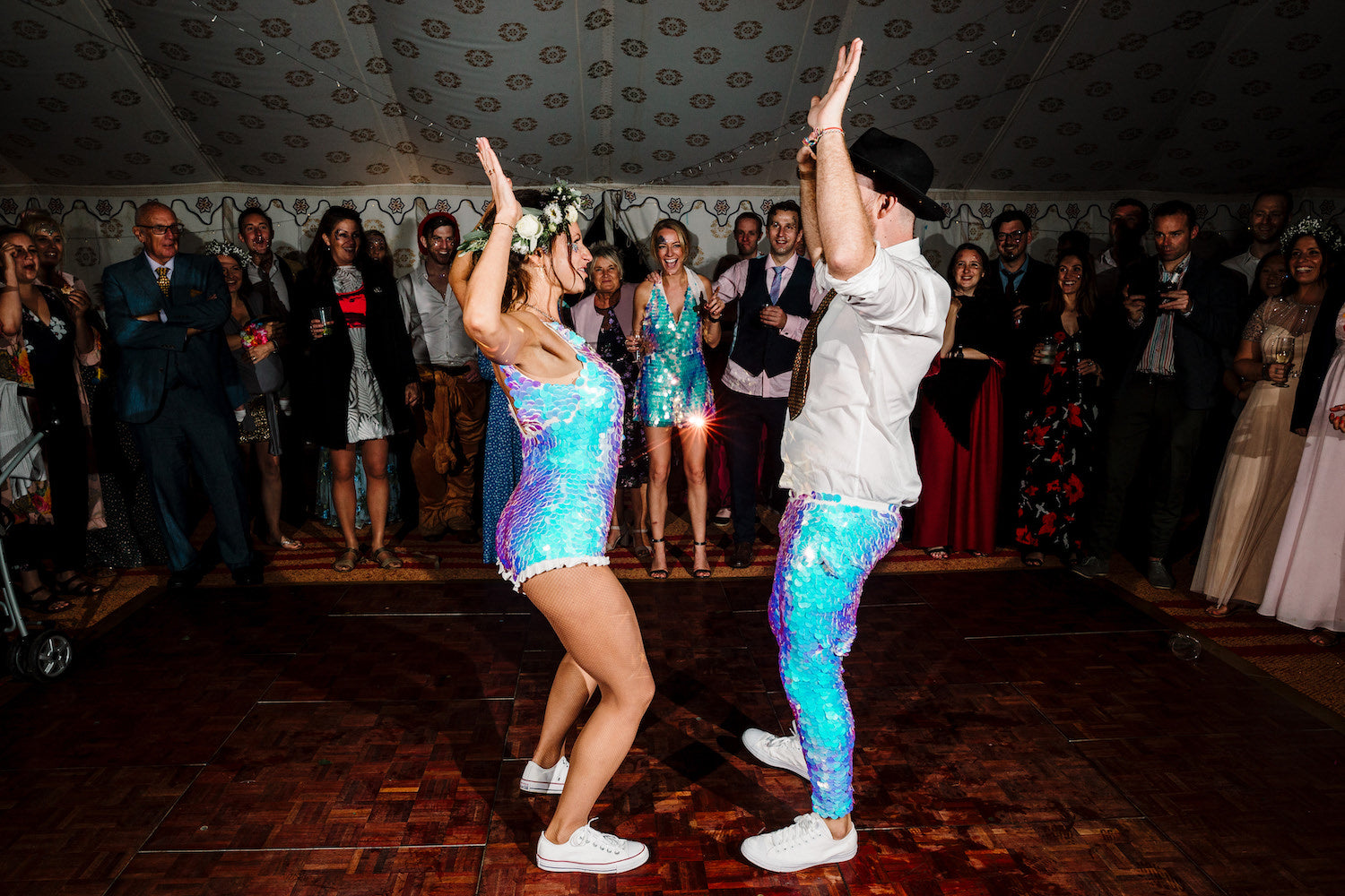 A bride and groom wearing matching white sequin outfits perform their first dance at thier reception.