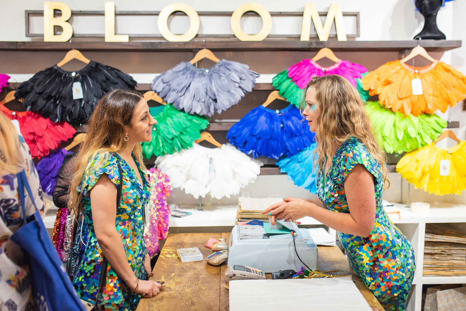 Two women wearing green sequin jumpsuits by slow fashion brand Rosa Bloom talk over the counter at the Rosa Bloom Pop Up Shop.