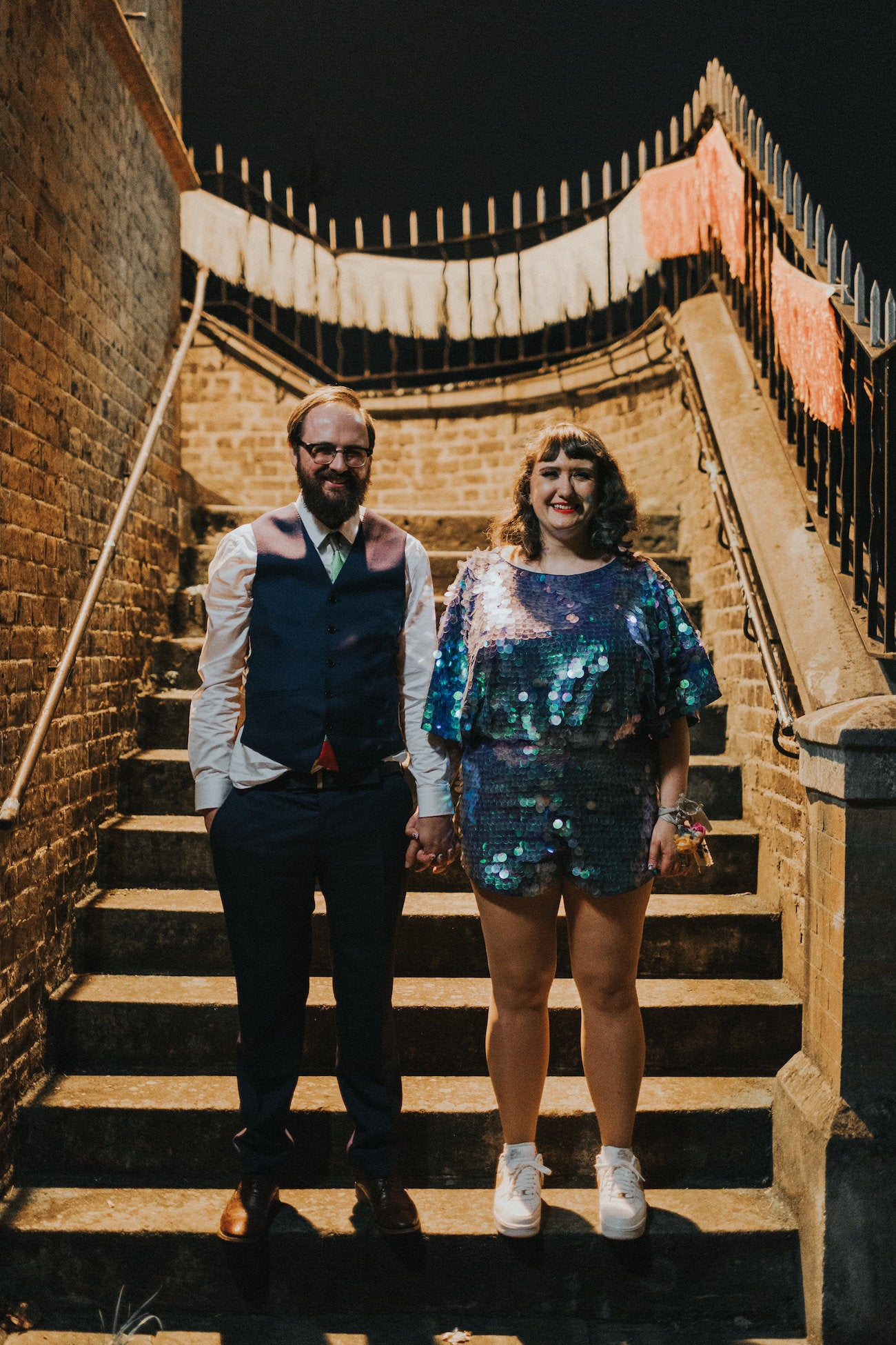 A newly wed couple pose for a photograph at night by some stone stairs and the woman wears a blue sequin romper.