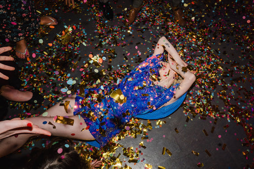 A bride wearing a festival style purple sequin romper lays on the dancefloor and is covered with confetti