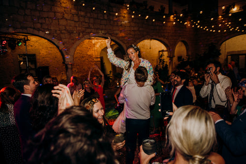A bride wearing a festival style sequin bomber jacket and glitter makeup is held up by her husband on the dancefloor