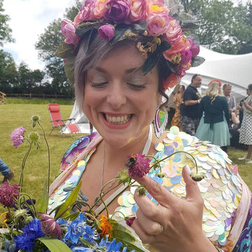 A bride wearing a festival sequin jumpsuit and headdress admires a bee in her bouquet.