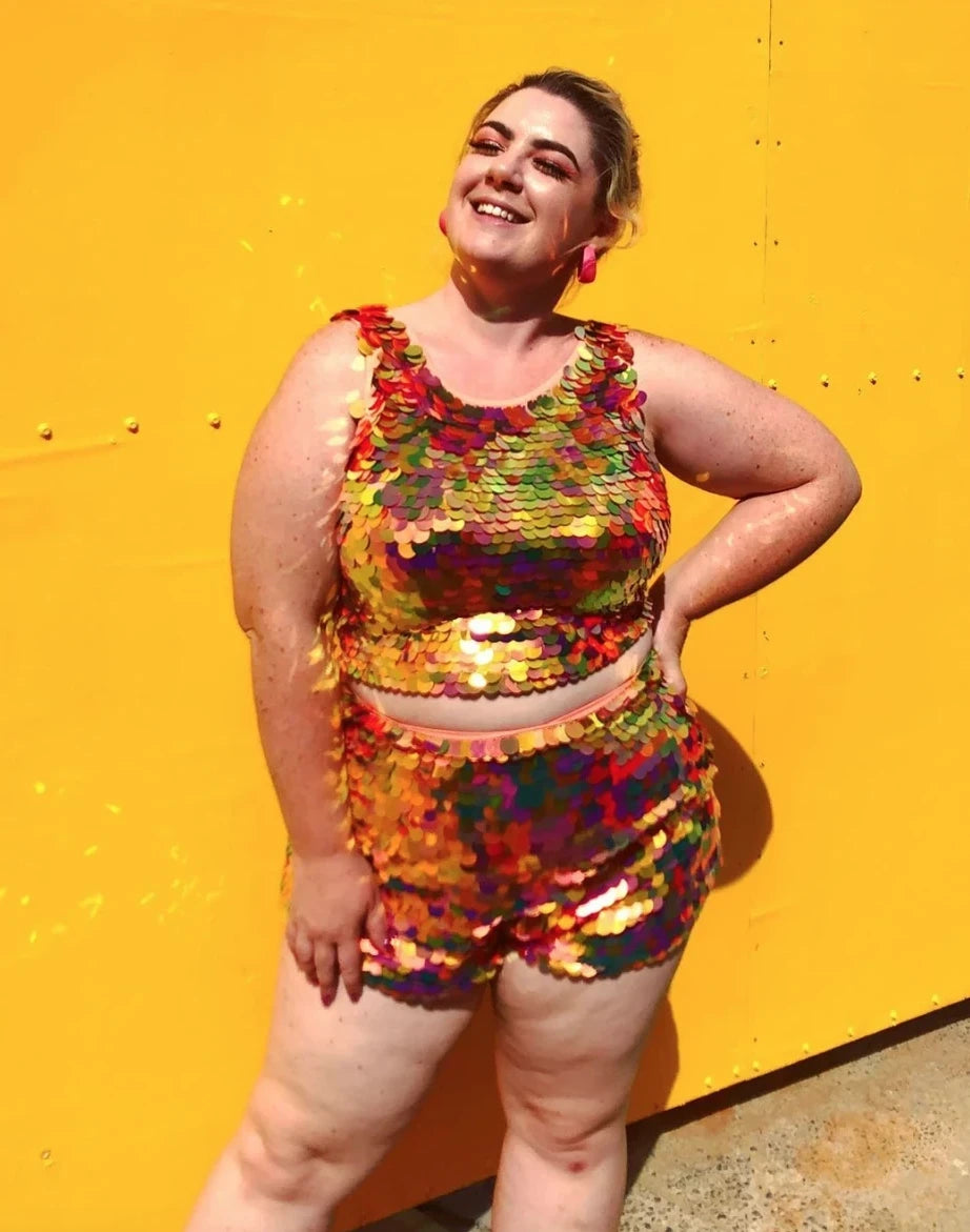 Woman in matching sequin outfit by Rosa Bloom poses against orange wall