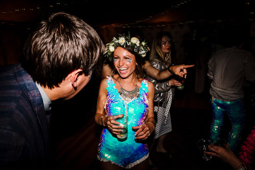A bride wearing a festival style sequin playsuit and floral headdress