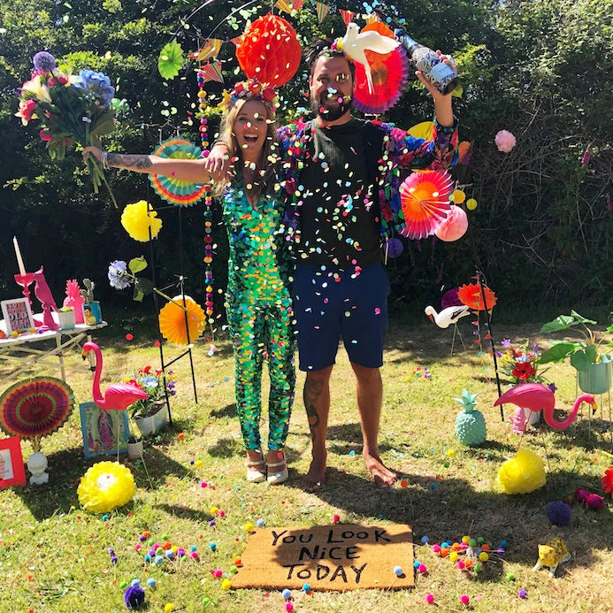 A man and a woman wearing a green sequin jumpsuit throw confetti in their garden