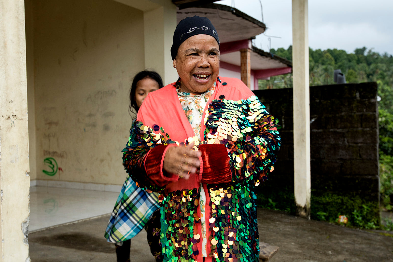 An Indonesian lady wears a kimono covered in green and gold irridecent sequins.