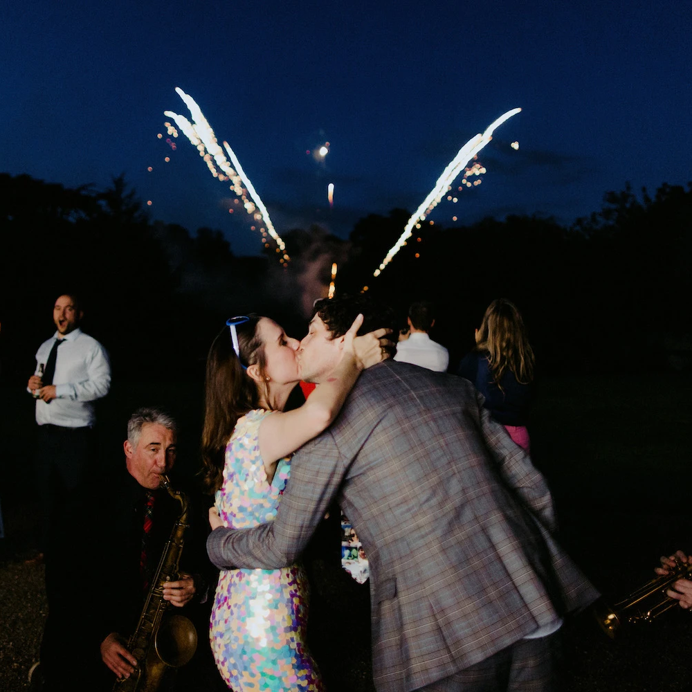 A bride wearing a festival style sequin jumpsuit kises her husband on their wedding day while fireworks go off in the background