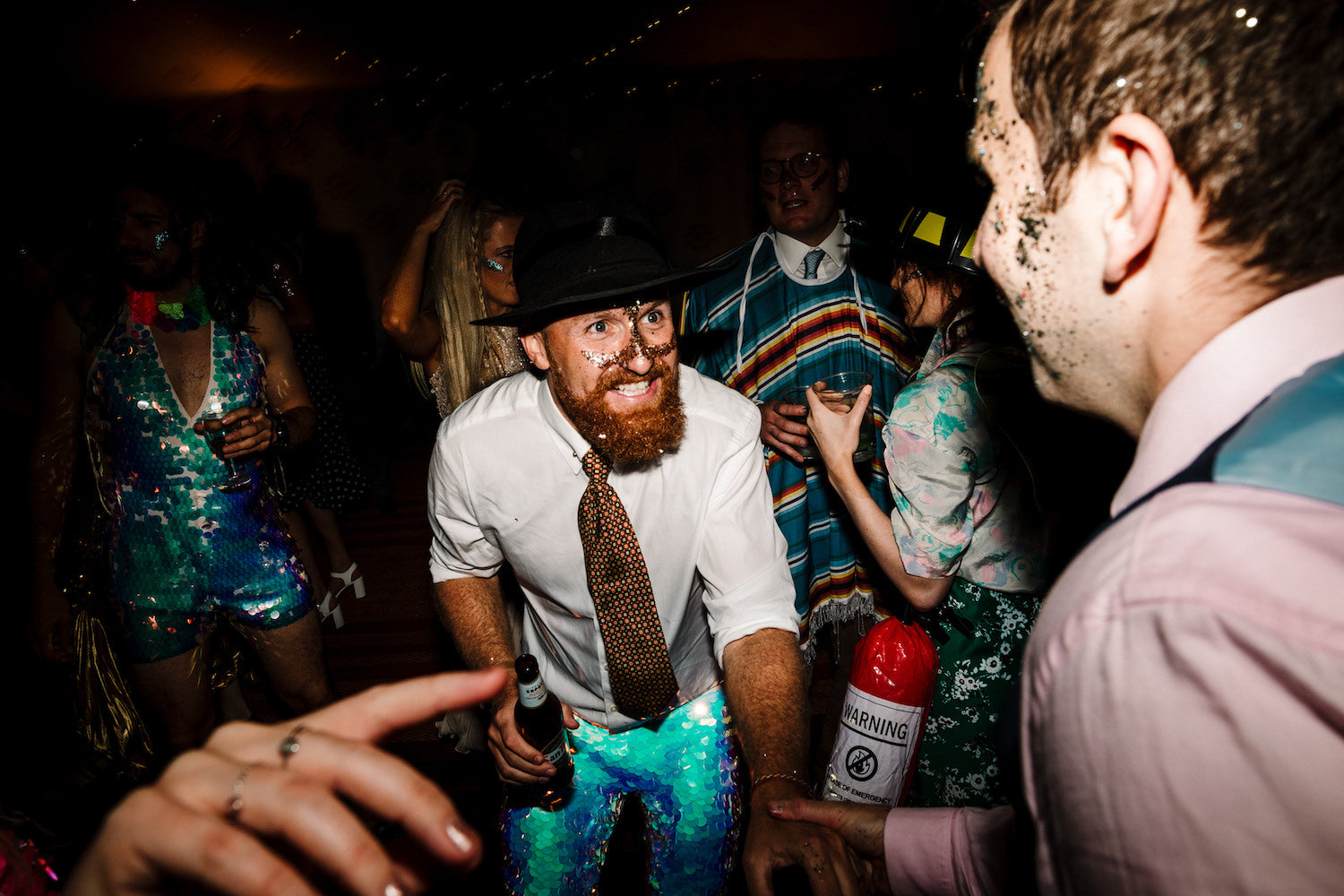 A groom wearing white sequin leggings a white shirt and a black hat is dancing with friends at his wedding reception