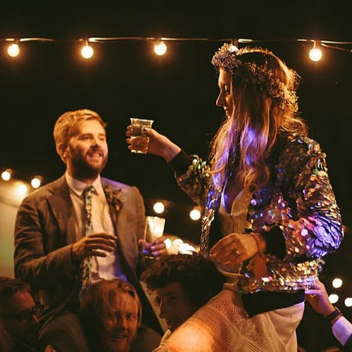 A bride and groom sit on the shoulders of their guests, the bride is wearing a festival style floral crown and sequin bomber jacket.