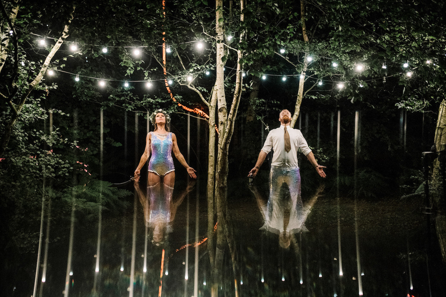 Bride and Groom wearing matching white sequin outfits stand with their arms open under fairy lights.