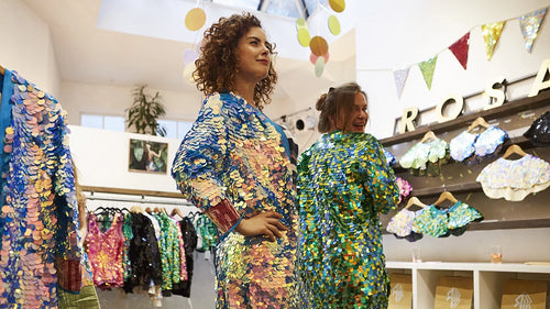 Shop customers try on green and blue sequin kimonos