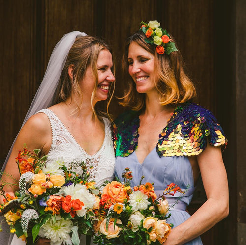 A bride stands with her bridesmaid who is wearing a purple sequin cape and a festival style floral headdress.
