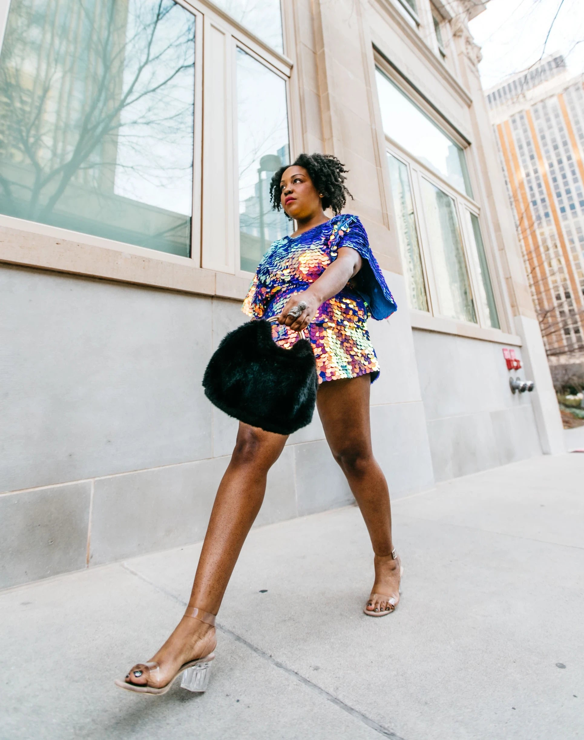 Woman in sequin romper by Rosa Bloom walks through Oklahoma city