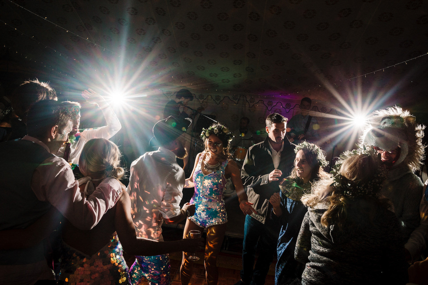 A bride and groom wearing matching white sequin outfits dance together surrounded by friends at their wedding reception
