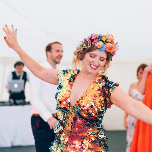 A bride with festival style flower crown and red sequin jumpsuit dances at her wedding