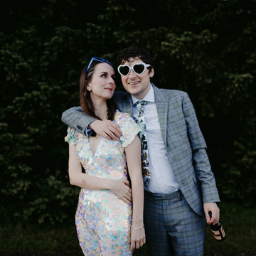 A bride wearing a festival style white sequin jumpsuit poses with her husband who is wearing a suit and sunglasses
