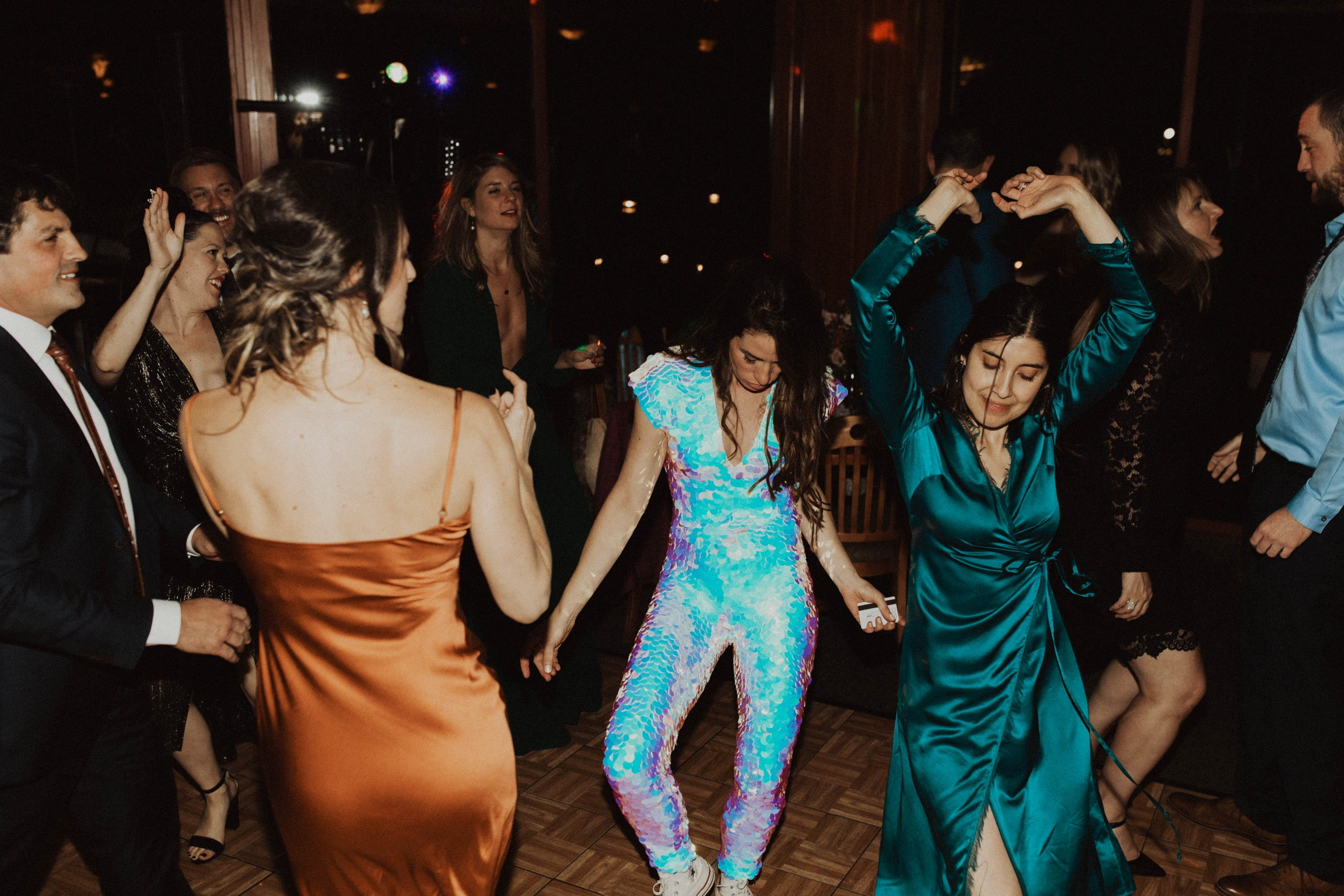 Woman in Opal sequin jumpsuit dances with friends at her wedding