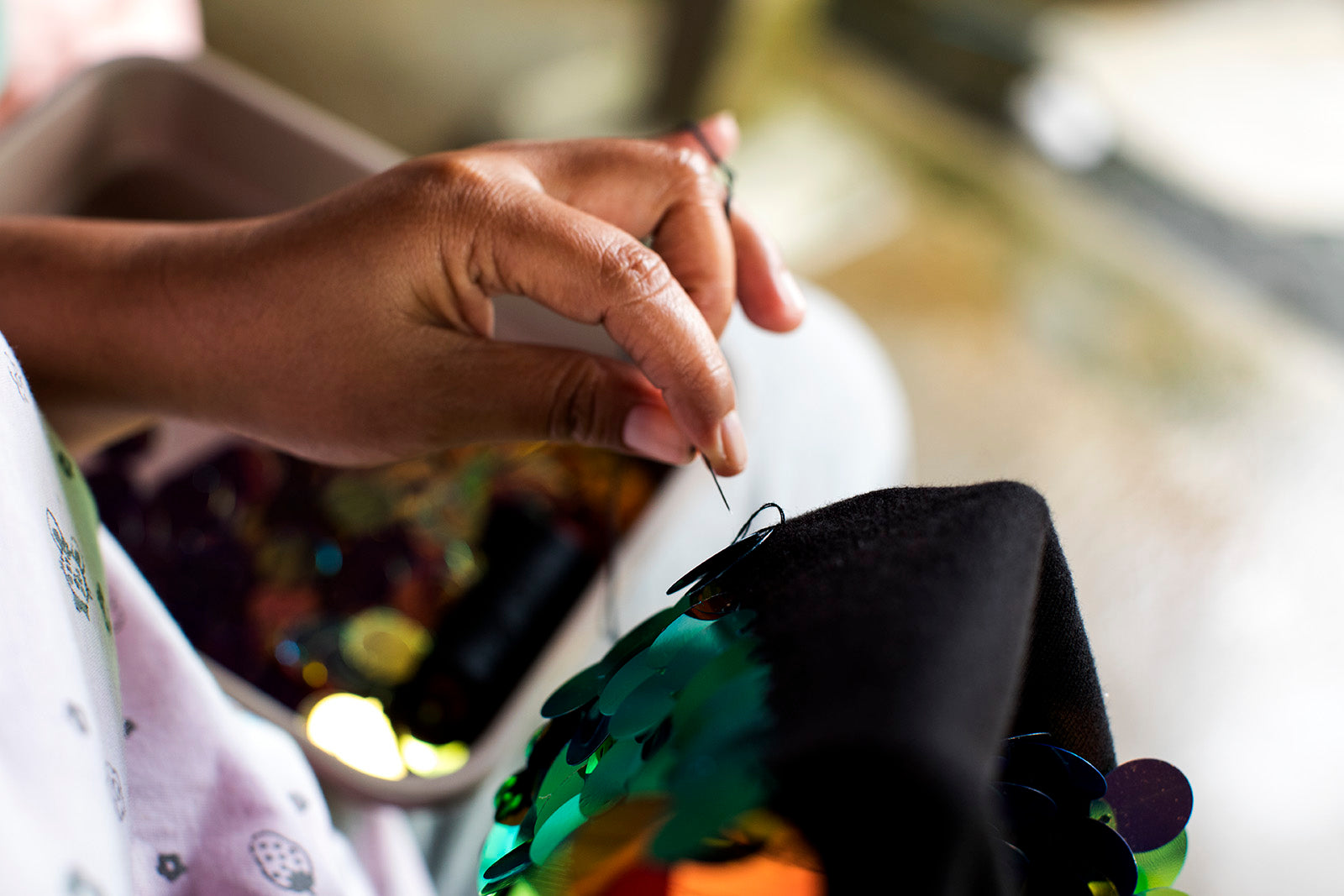 Close up shot of a woman's hands as she sews sequins on to black fabric.