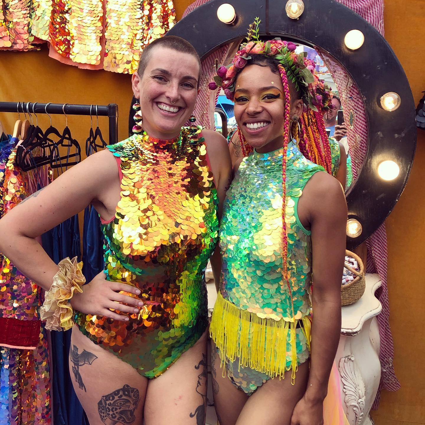 At glastonbury festival two friends pose in sequin leotards