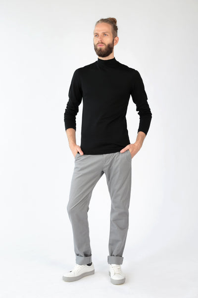Men's slim fit mock turtleneck sweater in black merino_ model wearing turtleneck sweater and trousers