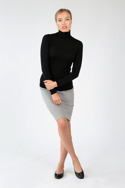 Women's turtleneck top in ultrafine black merino by Feelwear_ model wearing top and skirt