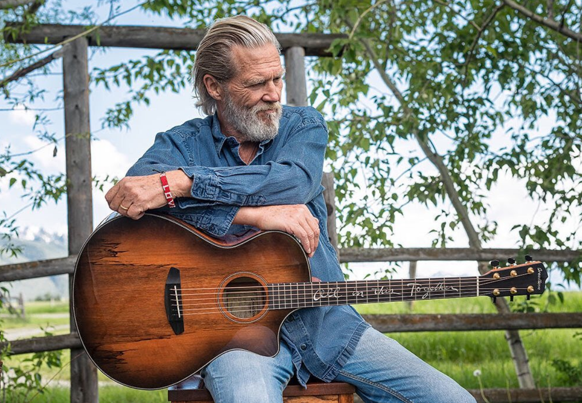 Actor Jeff Bridges with a guitar and love bracelet on his wrist sitting on a farm fence looking at distance